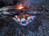 具材をつめた缶を焚き火にくべる